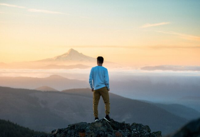 What men crave - a man standing on a mountain looking out onto the view