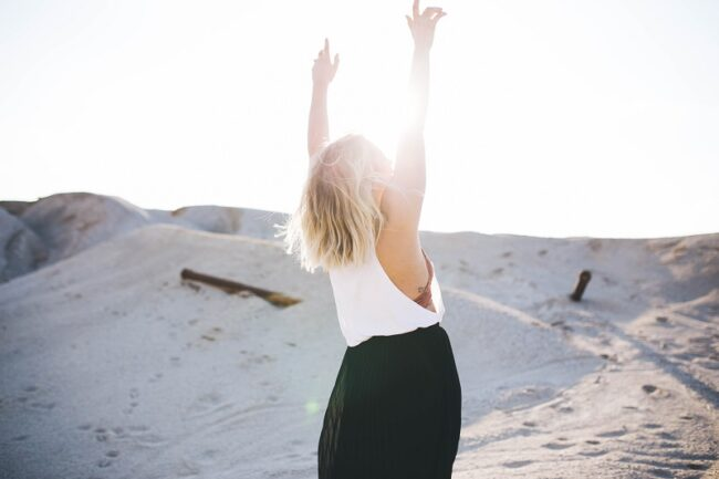 woman with her hands in the air enjoying the sun