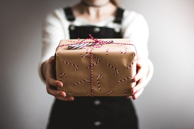 Quality time is your gift to someone. A woman holding a wrapped present.