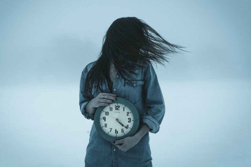 Take time for yourself - woman holding a clock