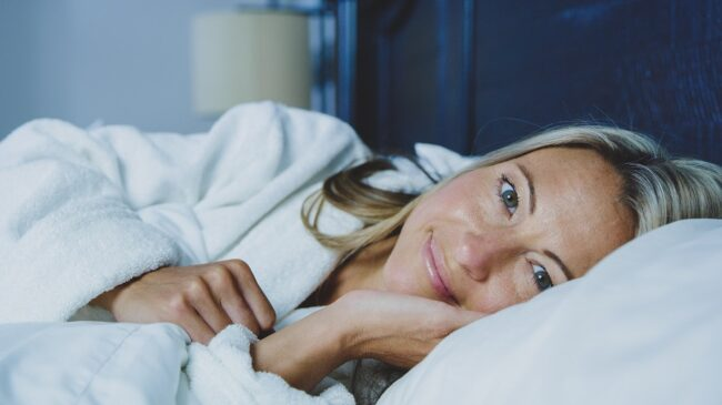 Tossing and turning - Picture of a women in bed relaxed and smiling.