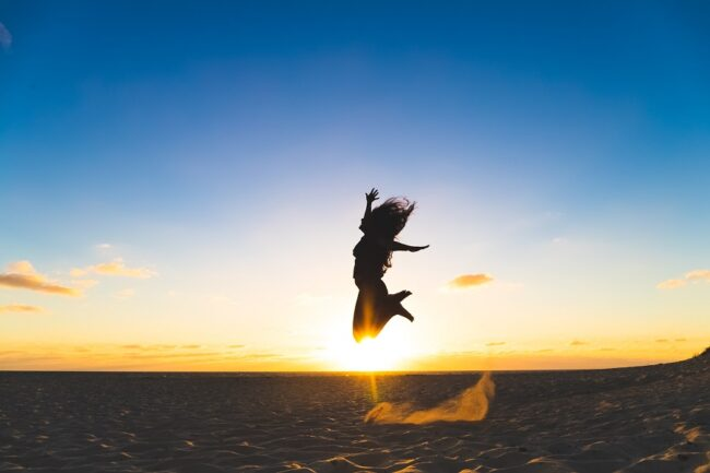 Your soul's purpose - a woman jumping up into the air feeling empowered.