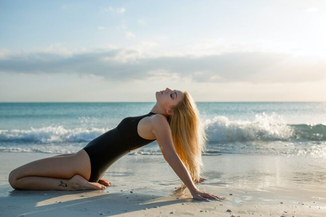 Emotionally aware - a woman on the beach embracing her body