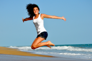 coping with emotions - a woman super happy and jumping for joy!