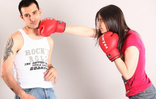 How to manage your emotions instead of fighting. A woman with boxing gloves hitting her man.