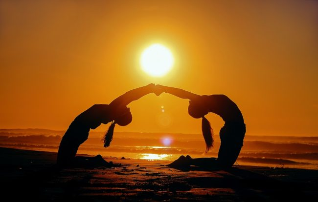 Marianne Williamson Quotes - picture of two people doing a back bend holding hands at sunset