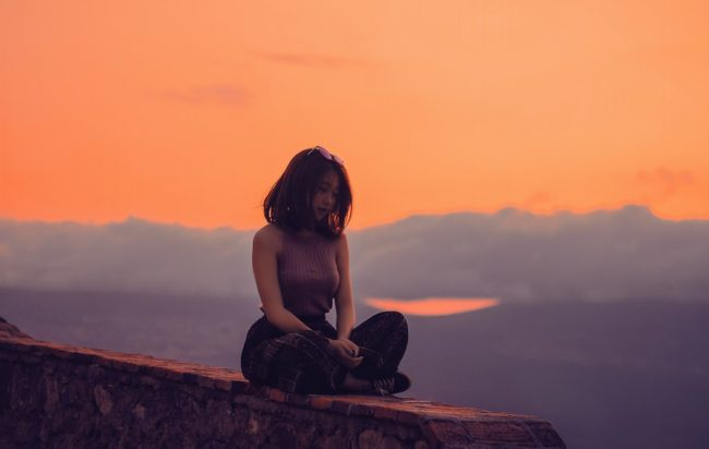 Marianne Williamson Quotes - picture of a woman meditating at dusk.
