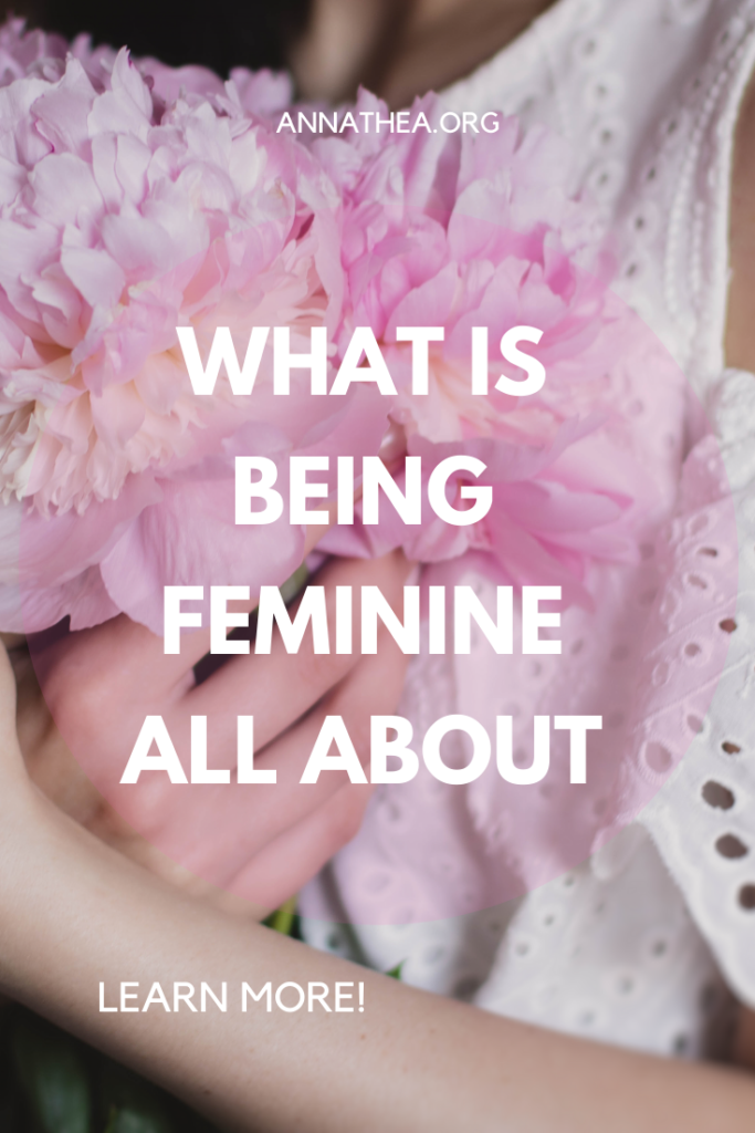 Being Feminine - A Pinterest Banner close up picture of a woman holding a flower with a caption of What is being feminine all about