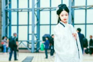 Yoni egg history - picture of a woman dressed in a traditional chinese attire in a modern airport.